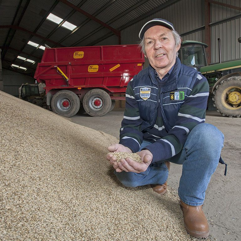 Farmer kneeling next to a pile of malt