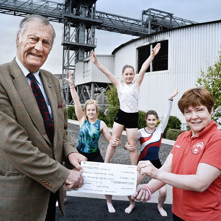 Simpsons Malt employee handing cheque to Berwick gmynastics club